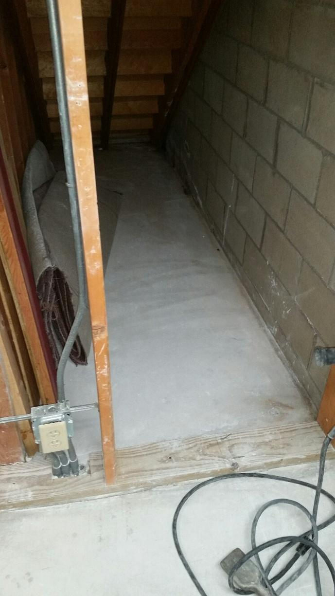 The alcove under the stairs will function as a new home for a SuperSump sump pump.