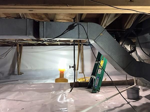 The crawlspace is fully encapsulated with CleanSpace Liner. The CleanSpace gives a bright, white, clean look to the space.
