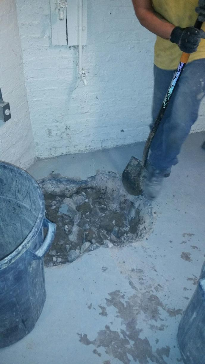 The team is carefully creating a space for the new sump pump.