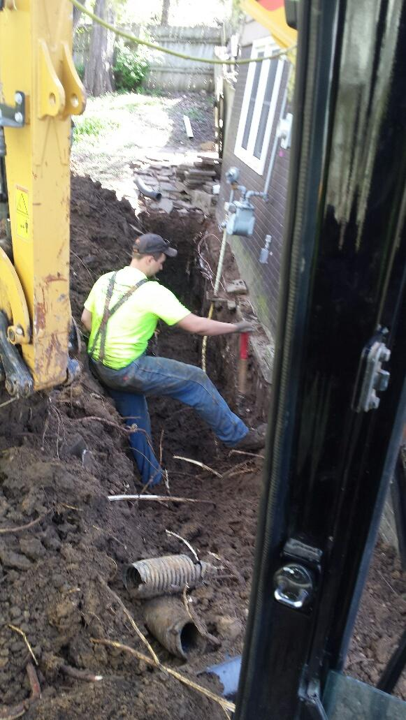 Crew members dig trenches to install Push Piers.