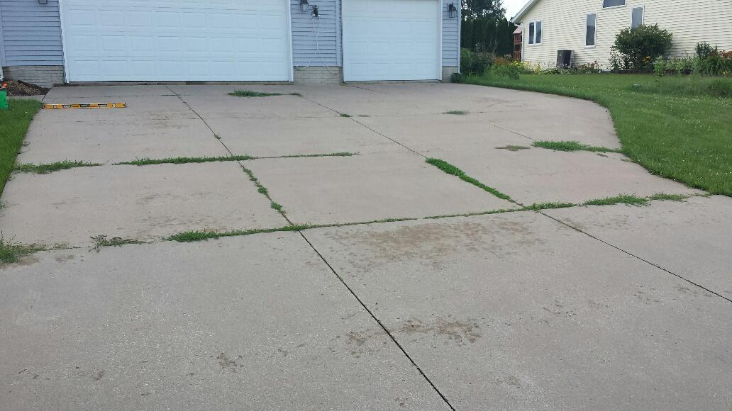 Overtime, the driveway slabs had sunken, allowing for weeds to grow in between the concrete.