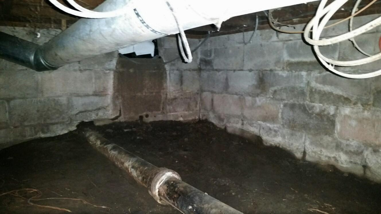 Dark, wet crawlspace makes it difficult for homeowner to access the water heater and furnace.
