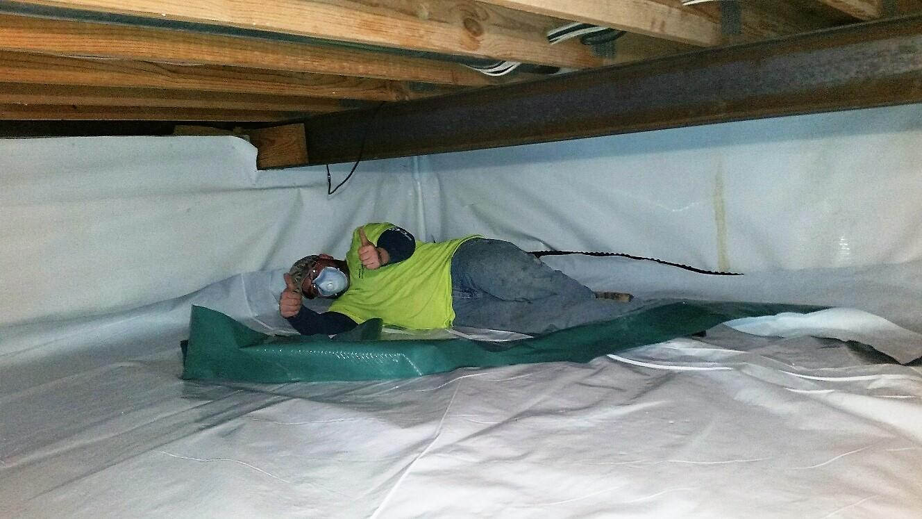 "Crewmen give ""thumbs-ups"" in helping protect the home from moisture and radon."