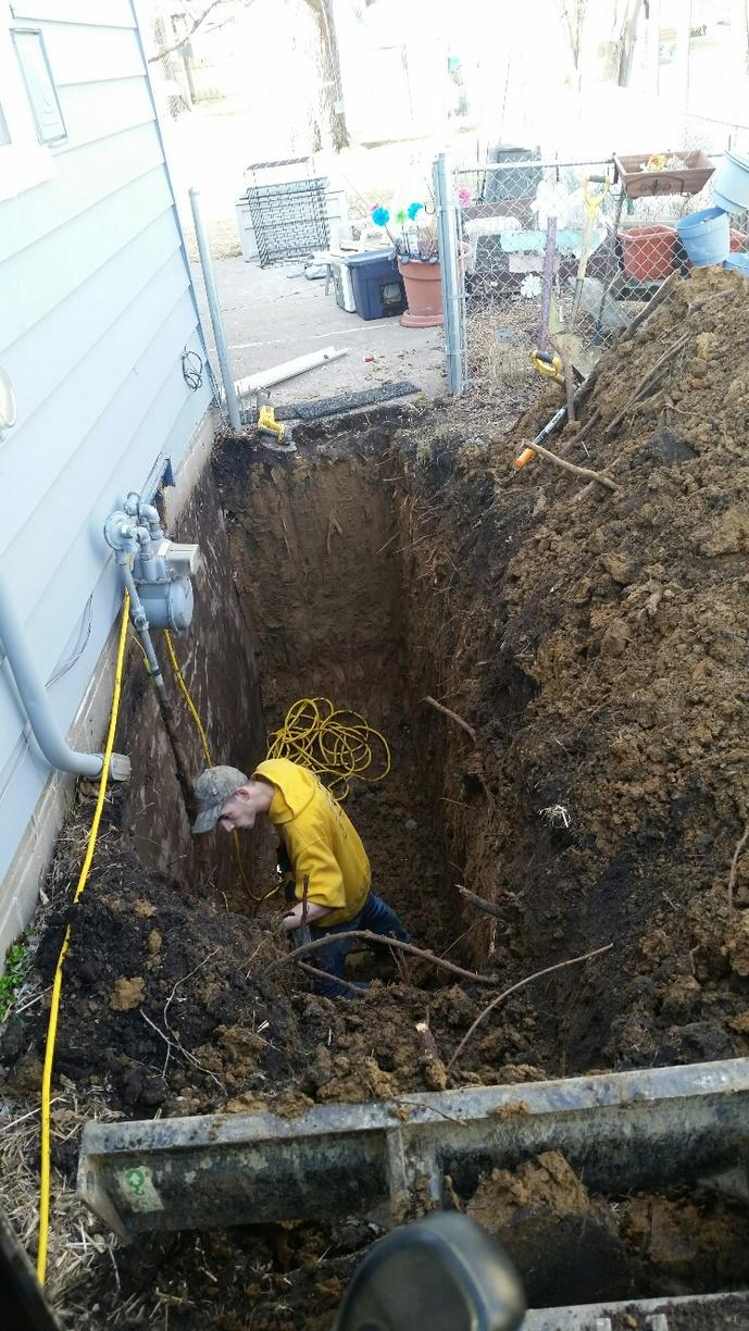 Dirt is excavated from around the foundation to attempt wall straightening.