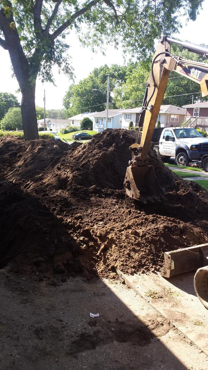 Crewmen begin excavating the dirt from around the home, releasing the ground pressure on the foundation.
