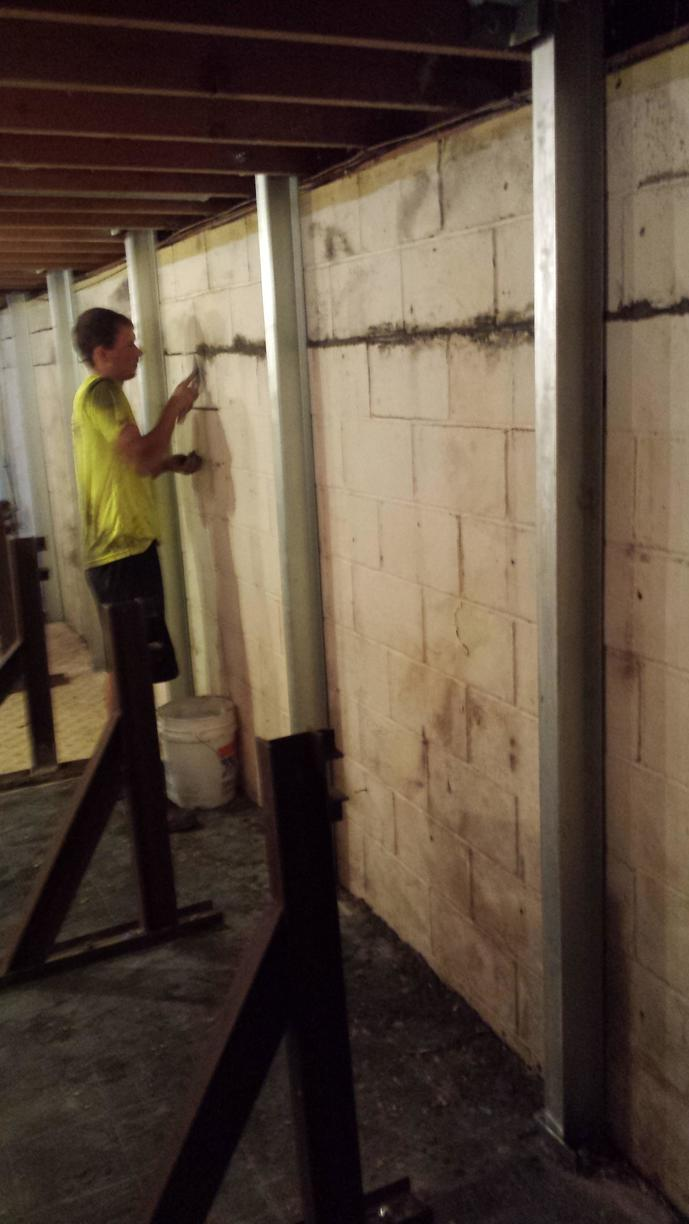 Extra support is applied to the walls to help the wall straightening act more effectively, while crewmen do some tuck pointing on areas of the foundation.