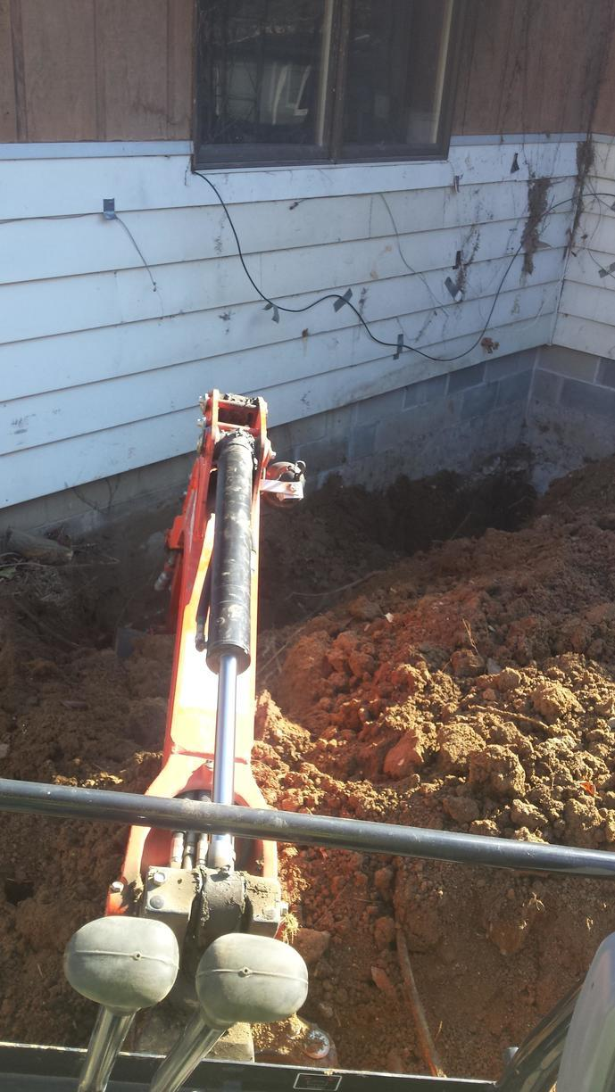 Dirt is replaced against the foundation, a job well done to stabilize the home.