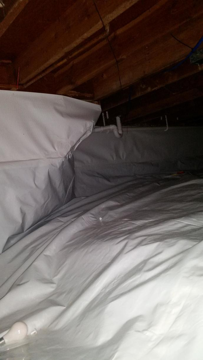 Workers place CleanSpace throughout the crawlspace, permanently sealing the area.