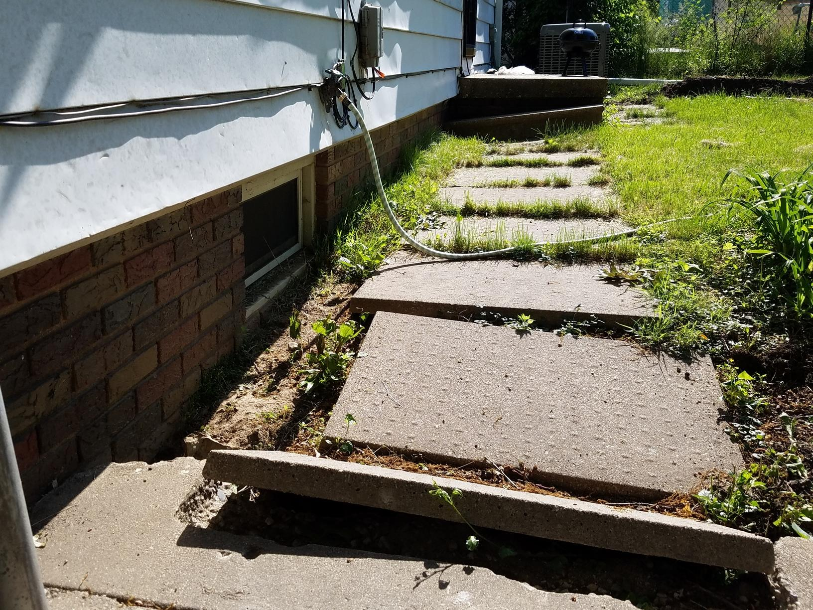 The sidewalk sinking and cracking due to foundation issues.