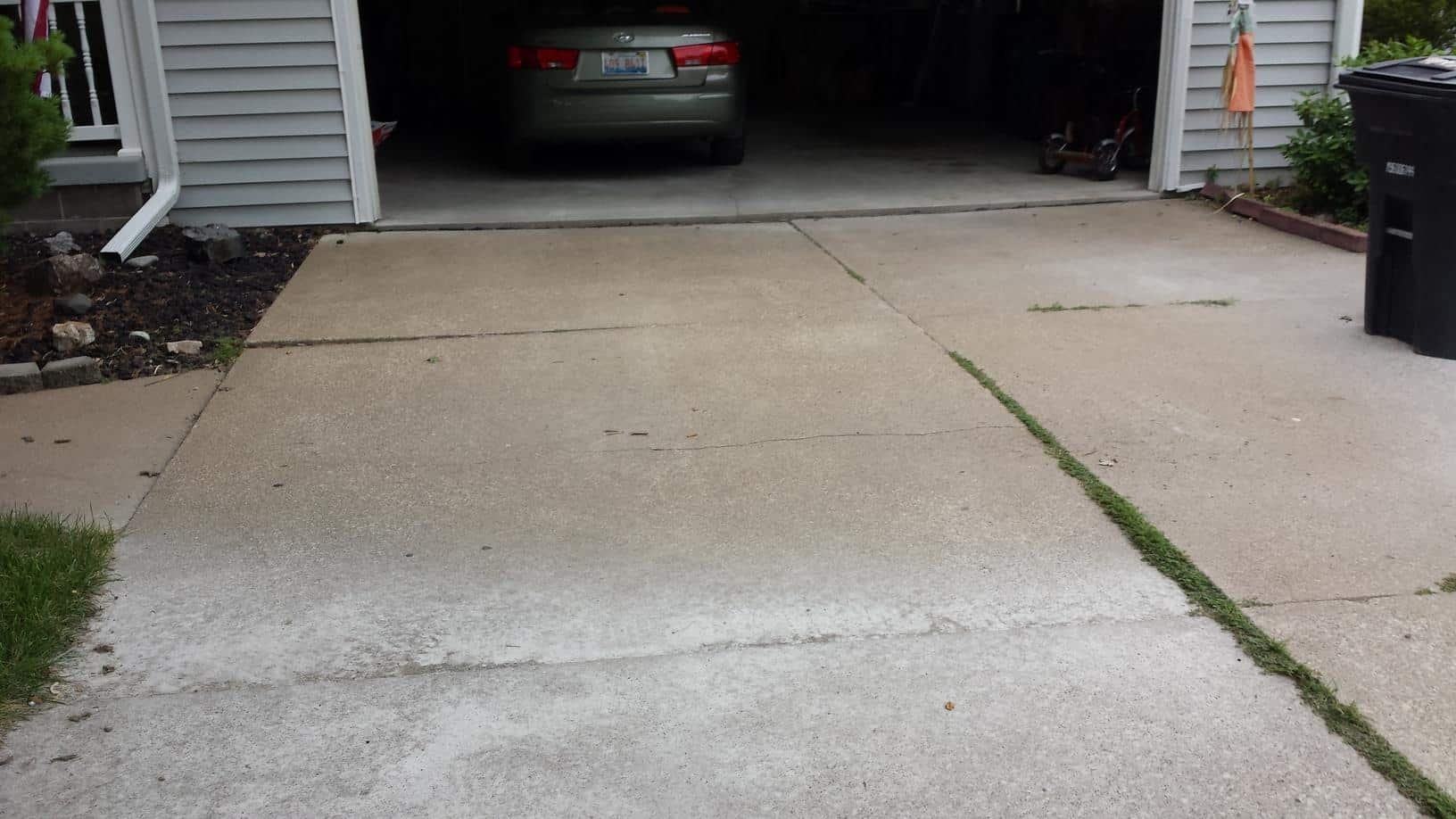 The cracking driveway slabs were starting to pull away from each other and gross grass in between.