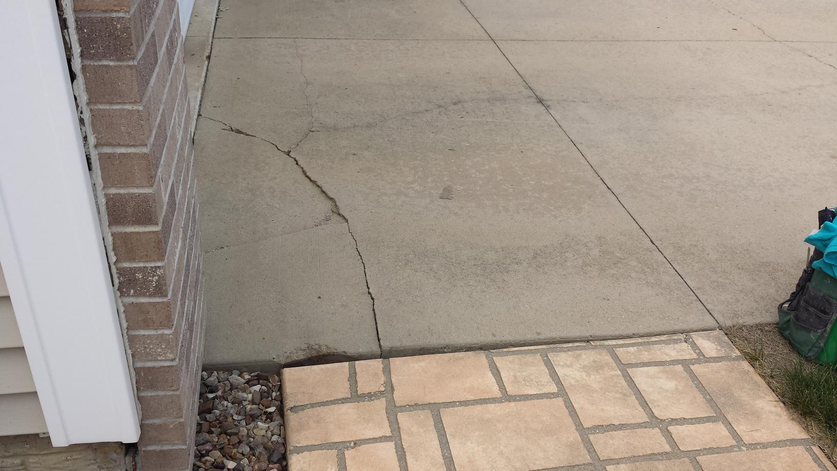 The sinking walkway caused the driveway to crack.