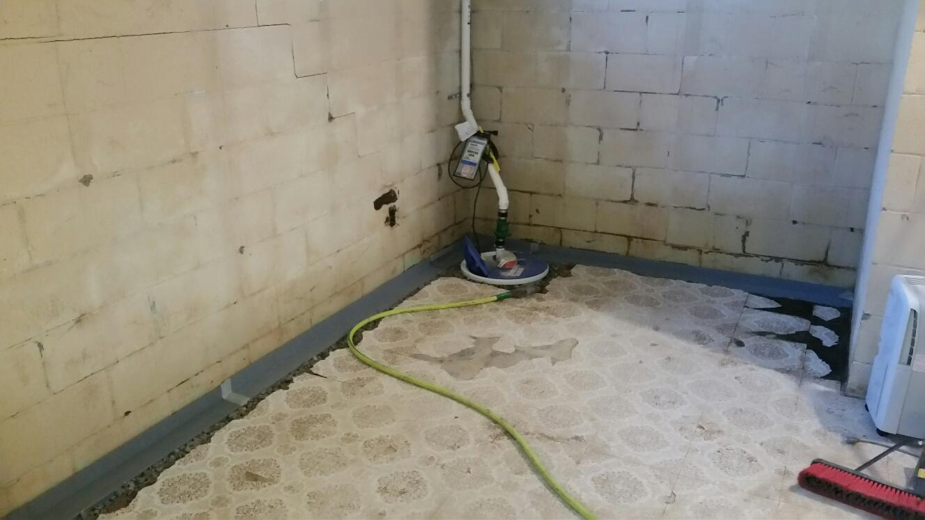 The team installs WaterGuard and SuperSump to waterproof the basement.