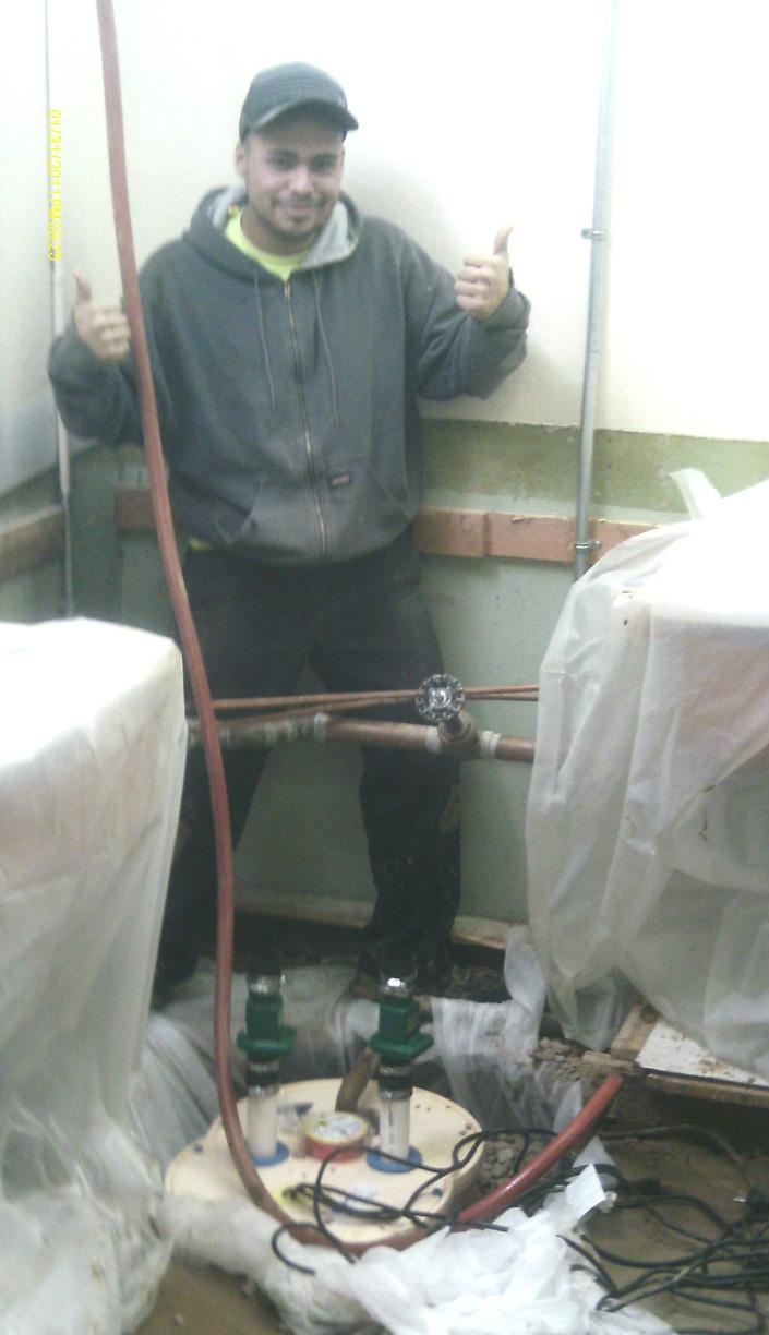 Team member gives the thumbs up while installing the TripleSafe sump pump system.