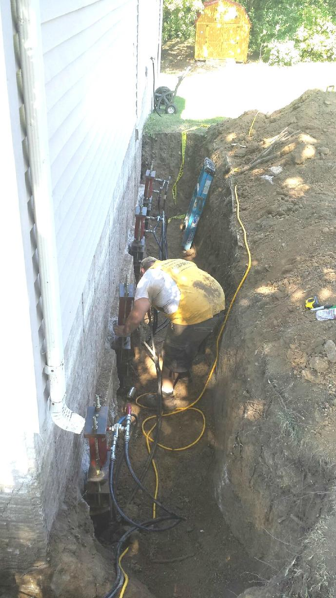 The team positions the steel brackets underneath the foundation footing.