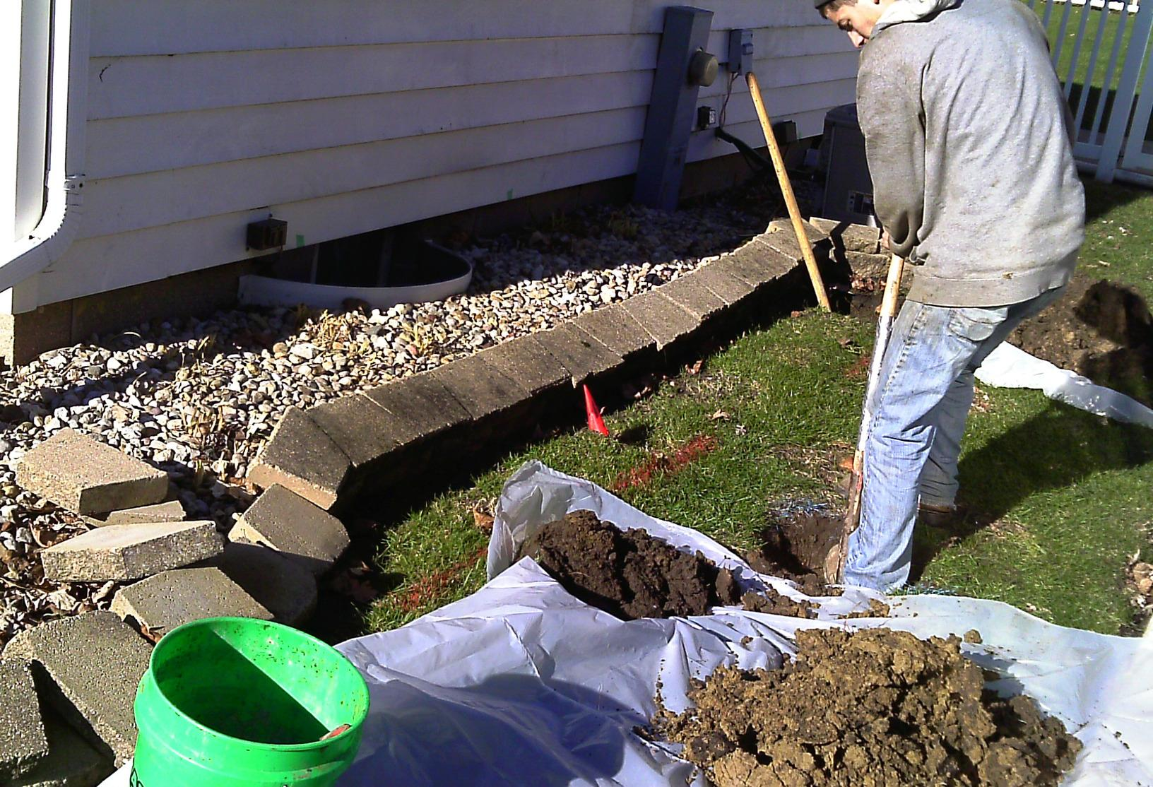 The team begins by digging small holes a few feet away from the compromised foundation to install the earth plates.