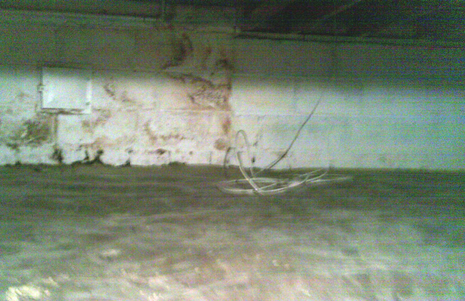 Water damage is visible from repeated water entering into this crawl space along the walls.