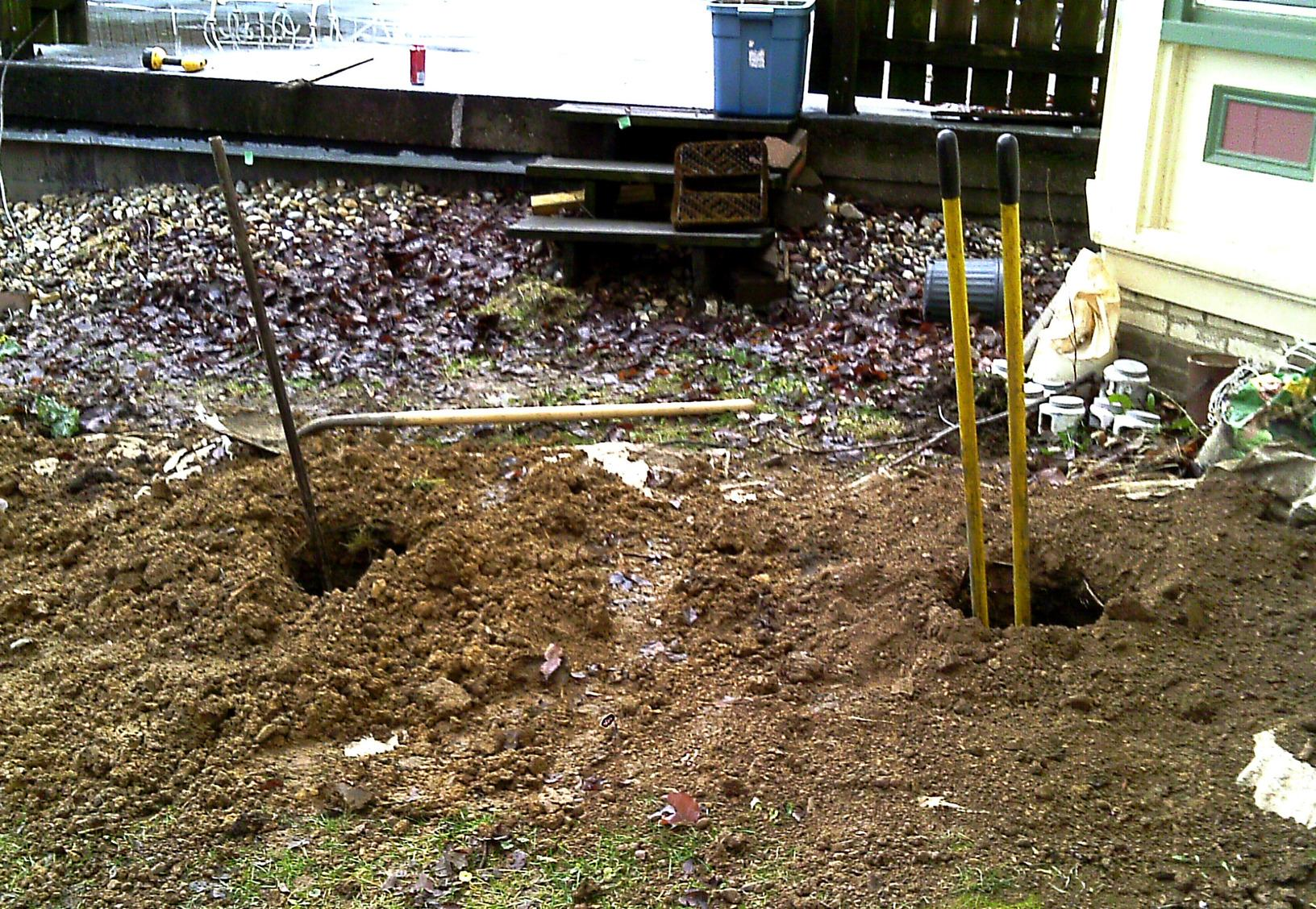 The team digs small holes a few feet away from the foundation where an earth anchor is seated within the hole.
