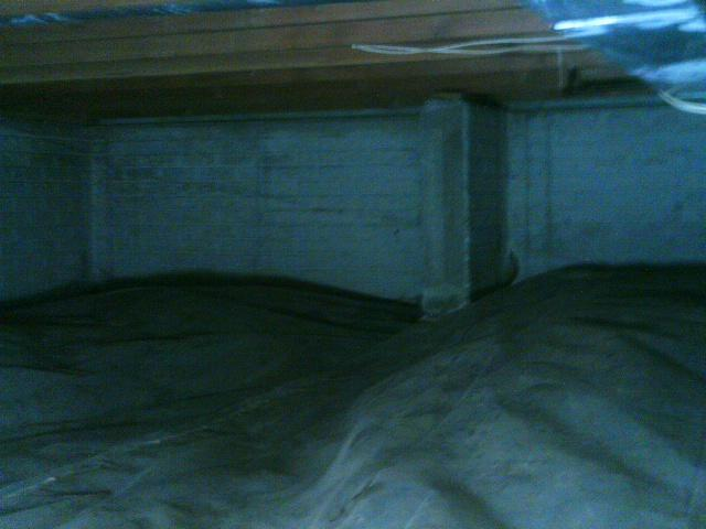 The crawl space with the old liner system was dark and wet.