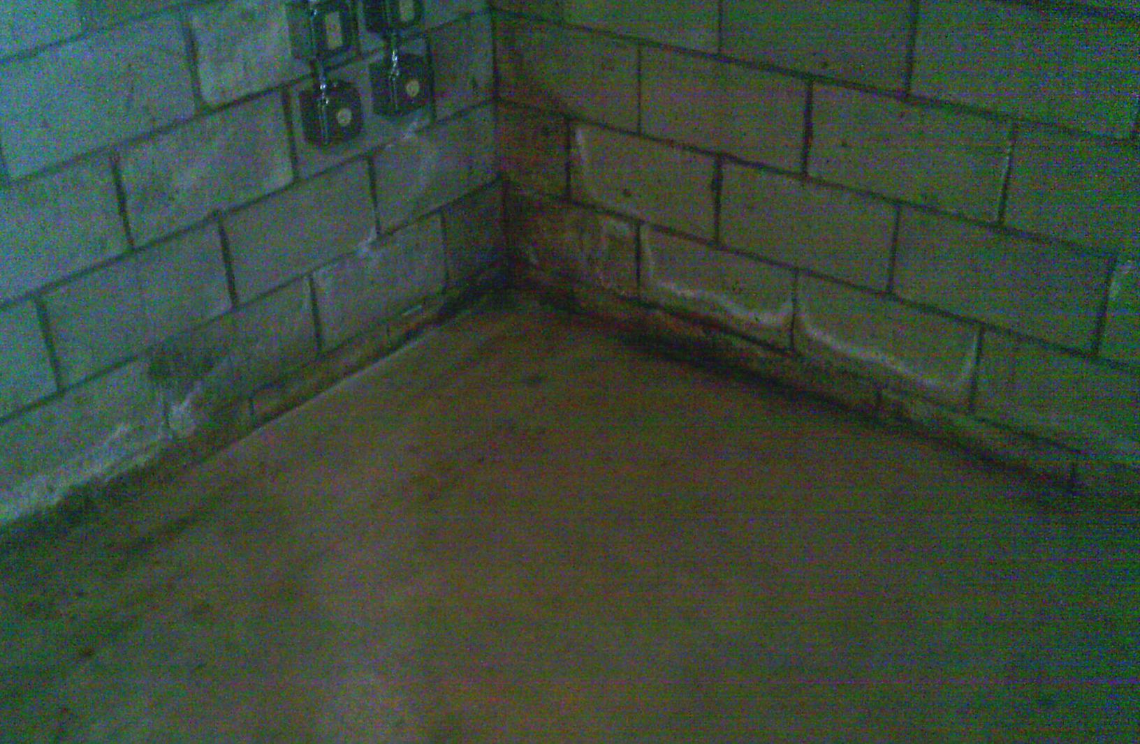 Signs of repeated water intrusion are evident by the marks in the corner and along the perimeter of the foundation floor.