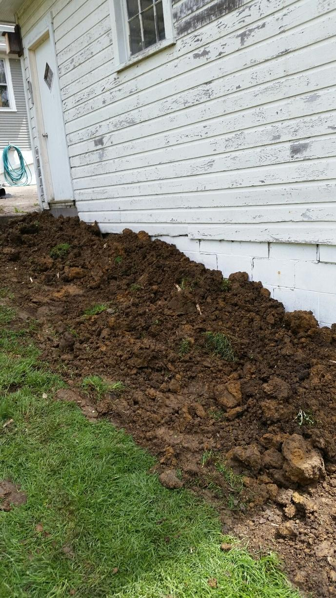 The dirt next to the house has been returned to its original position.