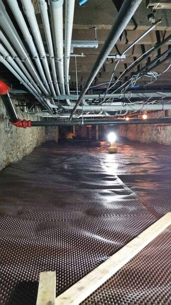 This image shows CleanSpace Drainage Matting in the large under-apartment crawlspace.