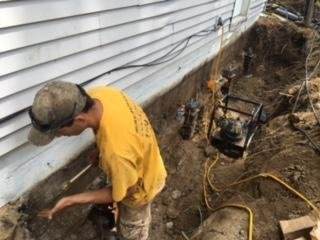 The team works hard to install the push piers to prevent further settlement of the home.
