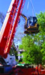 Lowering mini-excavator onto working surface below wall