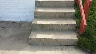 Sidewalk to the stairs has sunken, creating large gaps.